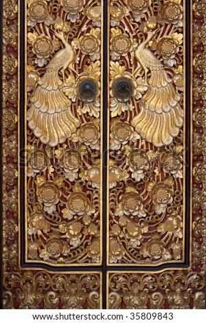 Tropical bird ornament on golden door in Bali, Indonesia - stock photo