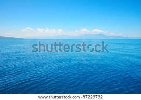 Tropical blue sea and blue sky with sun. Mountains on the horizon - stock photo