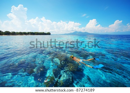 Tropical blue sea and young woman snorkeling over reef - stock photo