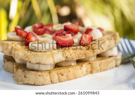 Tropical breakfast outdoor of French toast with bananas and strawberries - stock photo