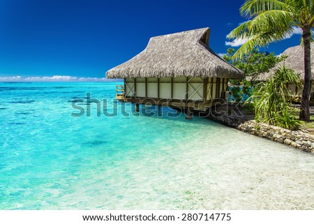 Tropical bungalow and palm tree next to amazing blue lagoon on the island - stock photo