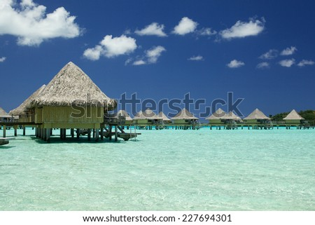 Tropical bungalow   in amazing blue lagoon - stock photo