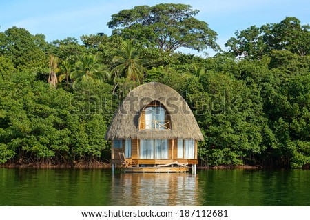 Tropical bungalow over water with thatched palm roof and lush vegetation in background, Bocas del Toro, Caribbean sea, Central America, Panama - stock photo