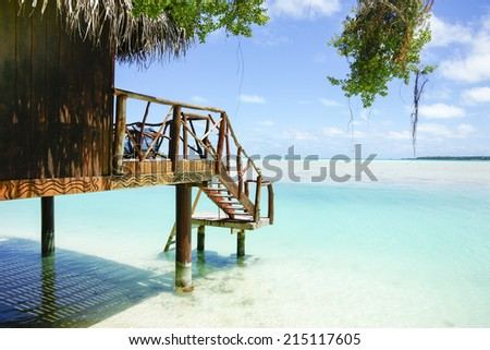 Tropical cabin over waters edge, Cook Islands, South Pacific. - stock photo