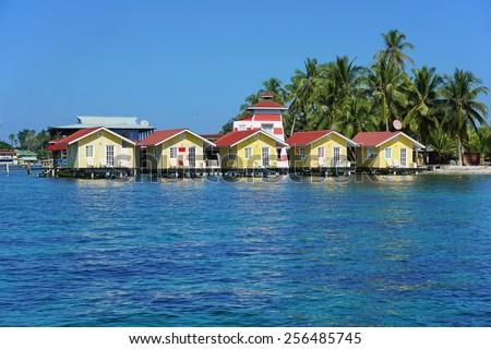 Tropical cabins over water of the Caribbean sea, Carenero island, Bocas del toro, Panama - stock photo
