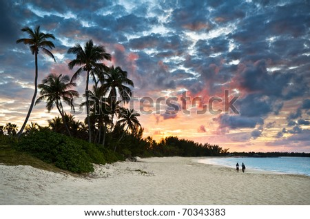 Tropical Caribbean White Sand Beach Paradise at Sunset with palm trees and tourists - stock photo
