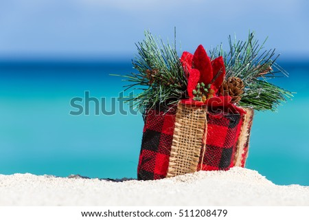 Tropical celebration on beach. Present box on sand against turquoise caribbean sea water
