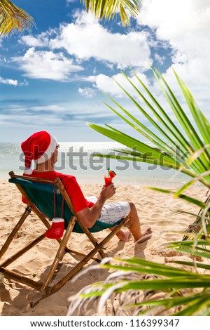 Tropical Christmas. Man in Santa's hat with cocktail sitting on chair on a beach under palm trees.