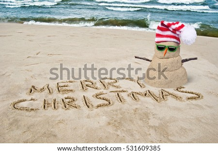 tropical Christmas snowman on beach with sunglasses and Merry Christmas sign written in sand