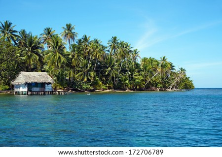 Tropical coast with a rustic Amerindian hut on stilts over the water, island of Bastimentos, Bocas del Toro, Panama, Caribbean sea - stock photo