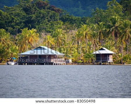 Tropical coastal house over the water with bungalow on stilts and lush jungle in background, Caribbean sea, Bocas del Toro, Panama - stock photo