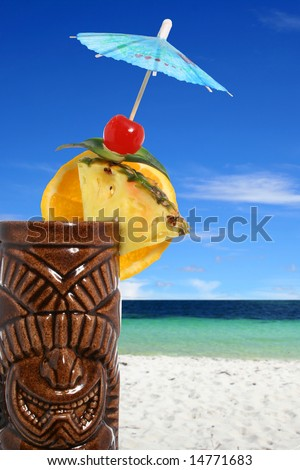 Tropical cocktail closeup with beach background - stock photo