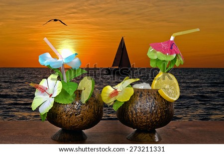 tropical cocktail drinks with fruit and flowers on wood with sailboat and sunset background - stock photo
