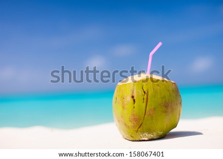 Tropical cocktail in a coconut on a beautiful beach - stock photo