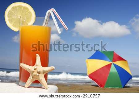 Tropical cocktail with starfish with parasol and beach - stock photo