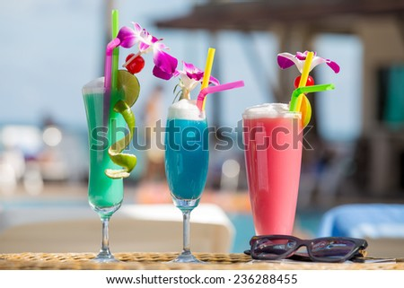 Tropical cocktails with sunglasses on a beach - stock photo