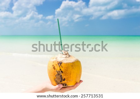 Tropical coconut cocktail with drinking straw on palm against a background of turquoise sea lagoon at exotic white sandy beach on paradise Holbox island in the Caribbean sea, Mexico. - stock photo