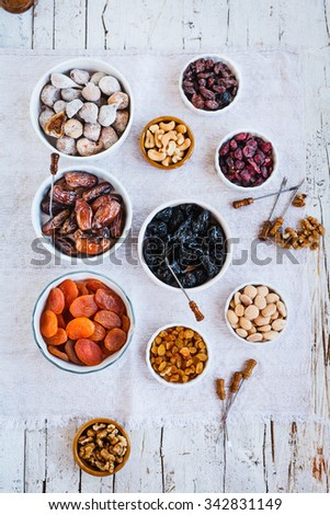 Tropical Dried fruits figs, apricot, plums, nuts, raisins, date palm three fruit in white bowl over old linen napkin. Middle eastern dried fruits for dessert.  - stock photo