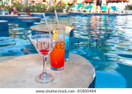 Tropical drinks at swimming pool on holidays - stock photo