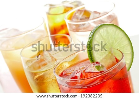 Tropical drinks in glasses with ice and a lime wedge. - stock photo