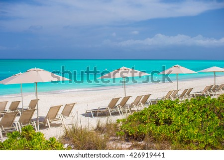 Tropical empty sandy beach with umbrella and chairs - stock photo