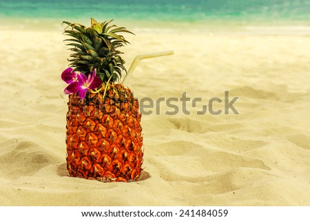 Tropical exotic pineapple cocktail at the beach overlooking the  white sandy beach and blue sea - stock photo