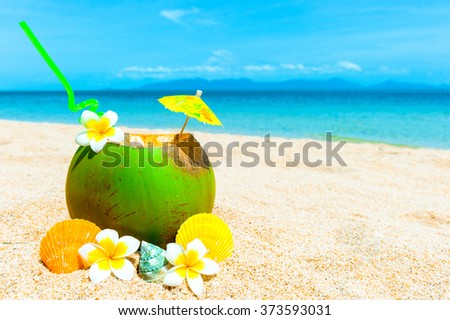 Tropical fresh coconut cocktail on white beach