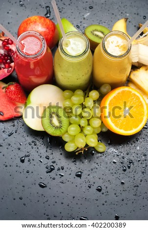 Tropical Fresh Fruits Juices Smoothie Bottles Red Green Orange Water Melon Strawberry Apple Kiwi Grapes Orange Mango Pomegranate Selective focus Black Background - stock photo