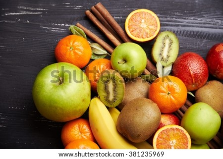 Tropical fruit and cinnamon sticks on black wooden background, top view. Selective focus. - stock photo