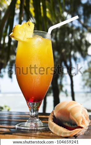 Tropical fruit cocktail and sea shell - stock photo