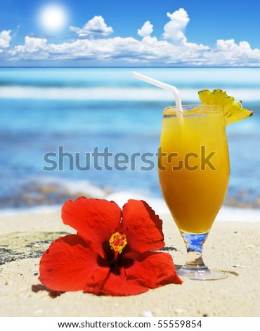 Tropical fruit cocktail on the beach - stock photo