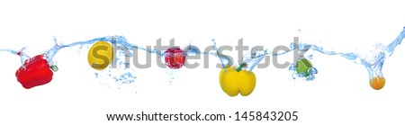 Tropical fruits and vegetables falling into water with splash isolated on white