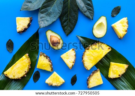 Tropical fruits background. Pinneapple and avocado slices, big leaves on blue background top view