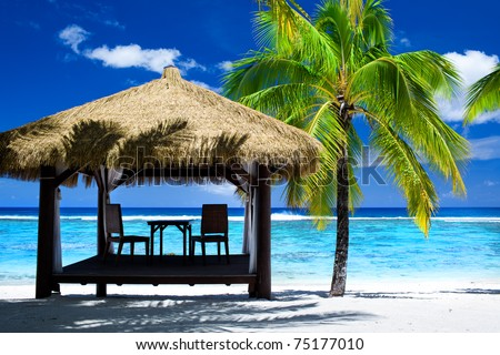 Tropical gazebo with chairs on amazing beach with palm tree - stock photo