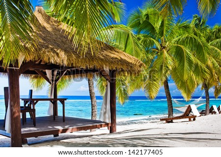 Tropical gazebo with chairs on deserted beach with palm trees - stock photo