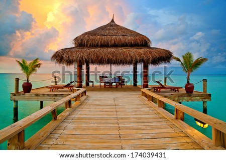 Tropical hut on water at sunset - romantic dinner in paradise - stock photo
