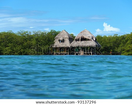 Tropical hut with thatched roof over the sea viewed from water surface
