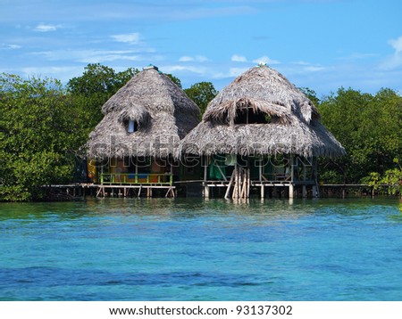 Tropical huts over the water with thatched roof, Caribbean sea, Panama - stock photo