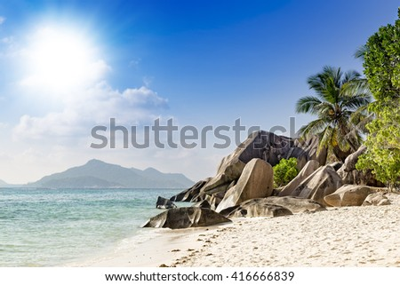 Tropical island beach white sand, palm trees, blue sky, famous anse source d'argent on La Digue, Seychelles islands. Shallow depth of field with focus on rocks. - stock photo