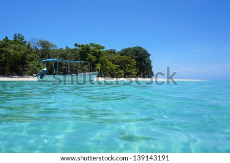 Tropical island beach with a boat on mooring buoy in turquoise water, Caribbean sea, Panama - stock photo