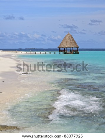 tropical island beach with jetty over turquoise ocean - stock photo