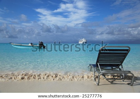 Tropical island beach with lounge chair, cruise boat and fishing boat - stock photo
