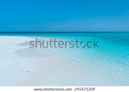 Tropical island in the Indian Ocean. White sand beach, blue sky and a strip of ocean - stock photo