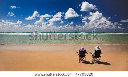 tropical island lonely sandy beach with clear warm water blue sky and two women sitting in chairs under sun - stock photo