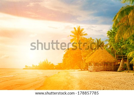 Tropical island sunset - stock photo