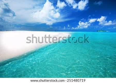 Tropical island with sandy beach with palm trees and turquoise clear water - stock photo
