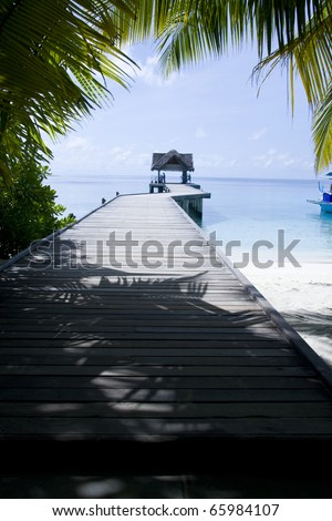Tropical jetty in Maldives over blue ocean. - stock photo