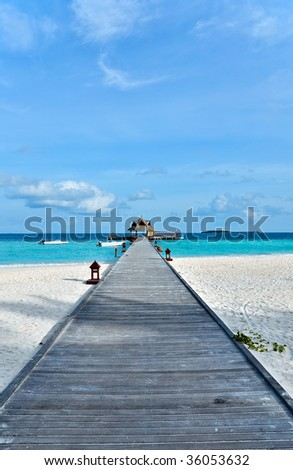 tropical jetty with boats over turquoise ocean - stock photo