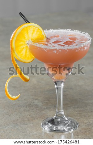 tropical juice in a margarita with a salt rim and an orange twist as a garnish - stock photo