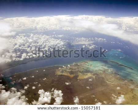 Tropical Land and Ocean through the clouds from above